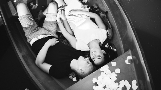loving young couple enjoying lying in a boat on the lake, rose petals