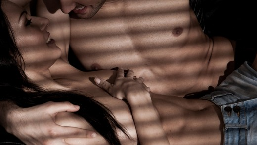 Loving couple in an intimate pose lying half naked in each others arms in a shadowed room