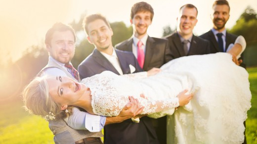 Outdoor portrait of young groom with his friends holding beautiful bride