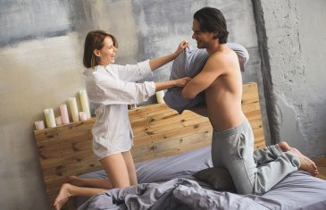 girlfriend and boyfriend playing and having a pillow fight in a bed