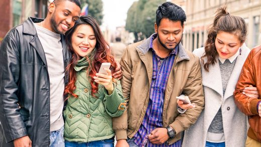 Multicultural row of friends walking together holding mobile smart phone outdoors - Interracial couples embracing to each other looking down at telephone - Friendship and modern technology concept