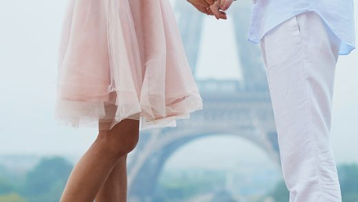 Couple having a date holding hands and kissing or hugging in front of the Eiffel tower in Paris. Unrecognizable people closeup of legs