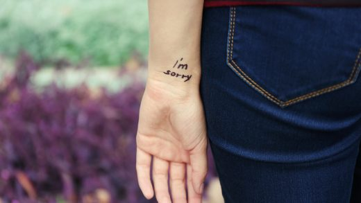 Hand of young woman with tattooed phrase on it, on flowers background, close-up