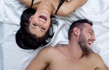 Erotica. Top view of loving couple laughing in bed